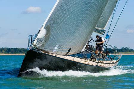 Een krachtige zwart racing yacht gevuld met wind zeilen bevoegdheden door middel van de kustwateren