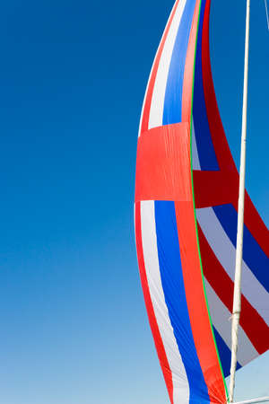 spinnaker: A red, white and blue spinnaker sail filled with wind Stock Photo