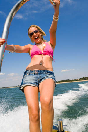 A stunningly beautiful and wealthy young blond woman holding on to the back of a powerboat and having fun photo
