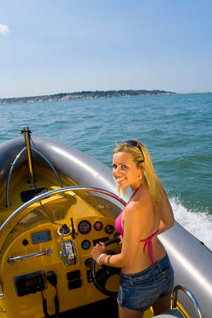 A stunningly beautiful and wealthy young blond woman driving a powerboat and having fun