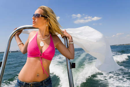 A stunningly beautiful and wealthy young blond woman holding on to the back of a powerboat with white material blowing in the wind behind her. Stock Photo