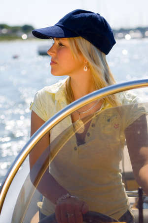 A stunningly beautiful and wealthy young blond woman driving a powerboat up a coastline lit by golden evening sunshine photo