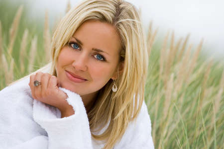 robe: A beautiful blond haired blue eyed model wearing a white towelling robe sits amid tall grass