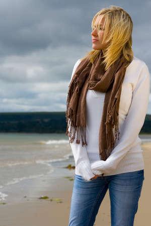 scarf beach: Una mujer joven eyed azul haired rubia hermosa que estaba parada solamente en una playa profundamente en pensamiento se encendi� por luz del sol de oro pero con los cielos tempestuosos detr�s de ella