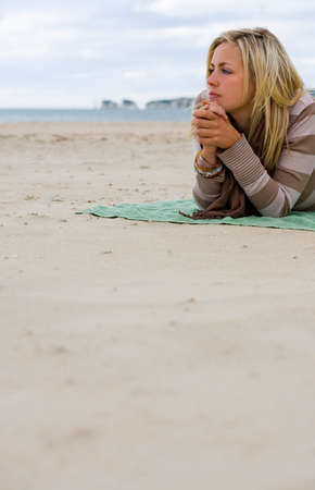 sad people: A beautiful blond haired blue eyed young woman laying alone on a beach deep in thought
