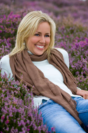 A beautiful blond haired blue eyed young woman laying amongst flowering heather and laughing photo
