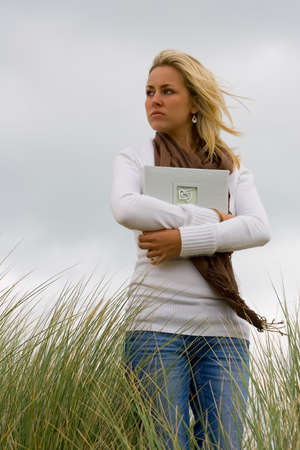 clutching: A beautiful blond haired blue eyed young woman stands amid long grass on a windswept headland clutching a book of memories