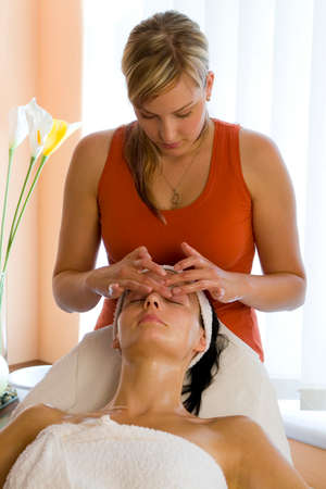 dark haired woman: A beautiful dark haired woman receives a facial treatment from a young blonde beautician
