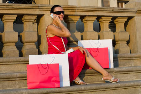 A classically beautiful Mediterranean woman sitting in the square of a European city surrounded by full shopping bags and chatting on her mobile phone photo