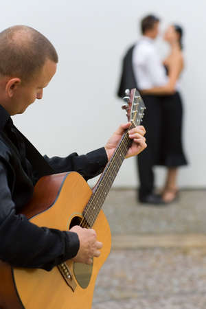 serenata: Un m�sico tocando su guitarra serenatas dos j�venes amantes