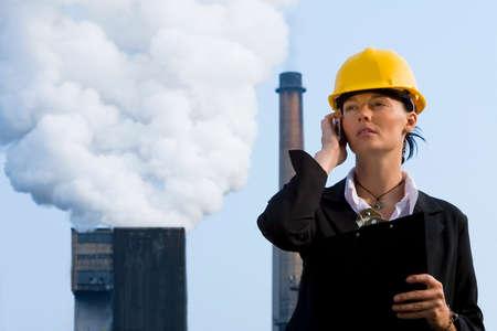 lluvia acida: Una hermosa mujer de pelo oscuro que llevaba un gorro duro y hablando por su m�vil mientras se est� frente a una f�brica de bombeo de la contaminaci�n de sus chimeneas
