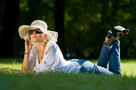 mobilephones: A beautiful dark haired woman laying in a sunlit wooded glade talking on her mobile phone