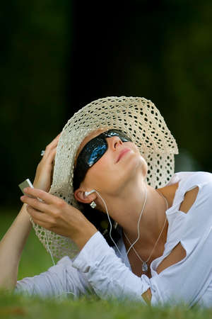 dark haired woman: A beautiful dark haired woman laying in a sunlit wooded glade listening to her mp3 player Stock Photo