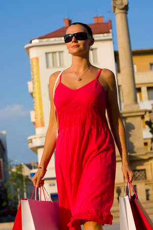 enigmatic: Un classico bella donna mediterranea camminando attraverso una citt� europea clutching piena borse per la spesa e sorridente un enigmatico sorriso  Archivio Fotografico