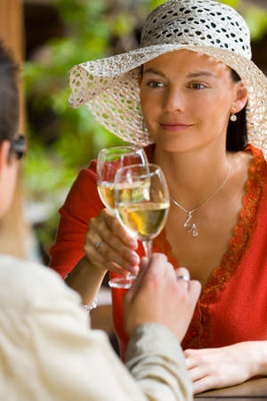 dark haired woman: A beautiful dark haired woman beautifully lit by summer sunshine shares a  drink with her man Stock Photo
