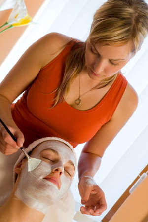 dark haired woman: A beautiful dark haired woman receives a face mask treatment from a young blonde beautician