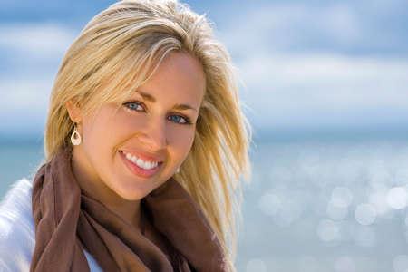 Cierre encima del retrato de una mujer rubia joven hermosa con el atontamiento de los ojos azules tirados delante de un mar chispeante