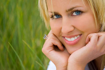 Close up portrait of a beautiful blond haired blue eyed model sitting and smiling amid tall grass Stock Photo