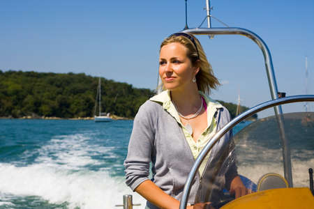 A beautiful young woman driving her powerboat around a mediterranean coastline photo