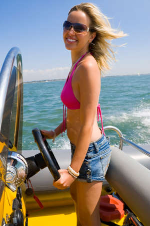 A beautiful young woman with wind in her hair as she drives her powerboat around a mediterranean coastline Stock Photo - 1650076
