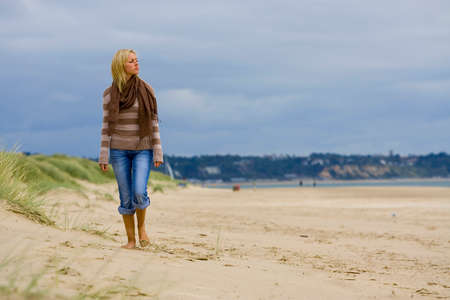 A beautiful young blond woman walks along a sandy beach