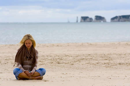 A beautiful young blond woman sits alone on a sandy beach listening to music