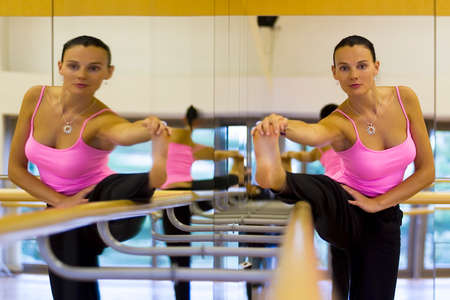 ballet bar: A beautiful young woman doing stretching exercises on a bar in a mirrored dance studio