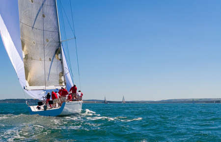 A fully crewed racing yacht sailing on a glorious summers day