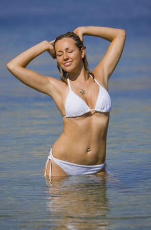erotic girl: A stunningly beautiful young blond woman enjoys the sunshine in a crystal clear blue sea
