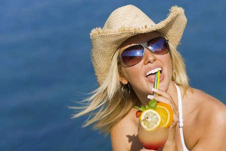 cappello cowboy: Stunningly bella bionda giovane donna in paglia cowboy cappello e occhiali da sole godendo un cocktail da un profondo mare blu
