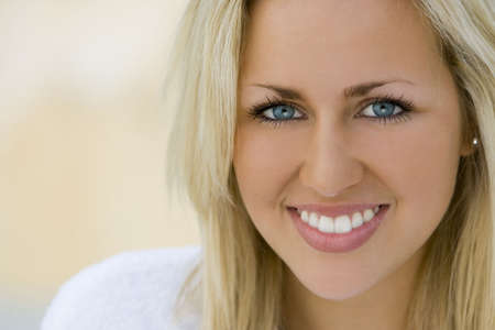 Close portrait of a beautiful young blue eyed blond woman wearing a bathrobe and bathed in soft natural light