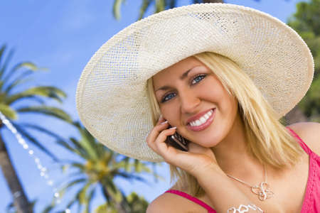 phonecall: An absolutely gorgeous blond haired blue eyed woman makes a phonecall on her mobile surrounded by palm trees in city square as a fountain runs behind her.
