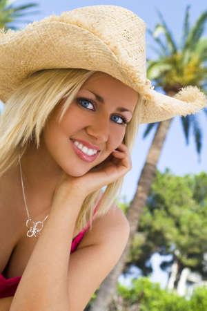 cappello cowboy: Assolutamente splendida bionda dagli occhi blu capelli giovane donna siede di fronte a ridere palme d'oro nel sole mentre indossa un cappello di paglia cowboy  Archivio Fotografico
