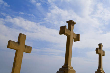 headstones: Three crucifix headstones shot against a dramatic blue sky Stock Photo