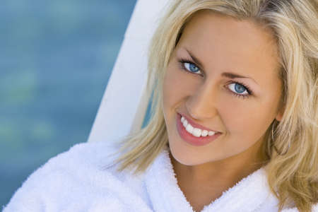 A beautiful young blond haired, blue eyed young woman sitting on a sun longer in front of a sparkling blue sea