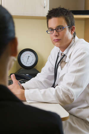 A female patient in consultation with a male doctor, visible behind him is a blood pressure monitor Stock Photo - 1832462