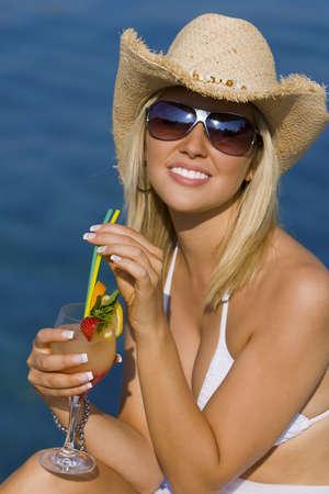 Una sentada rubia joven hermosa y feliz por el mar que bebe un coctel