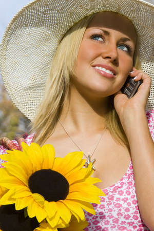 A beautiful young blond woman carrying a basket of sunflowers and talking on her mobile phone photo