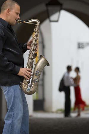 A street musician plays his saxophone while a romantic couple can be seen out of focus in the background photo