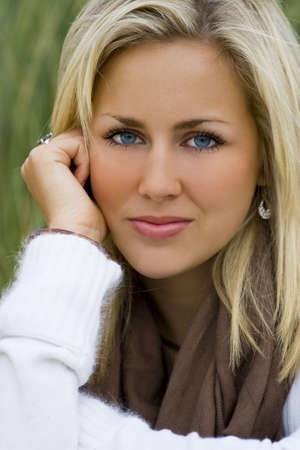 bionda occhi azzurri: Una bellissima giovane donna seduta rilassato e sereno tra erba alta