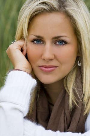 rubia ojos azules: Una hermosa mujer joven sentada relajado y sereno en medio de hierba alta  Foto de archivo