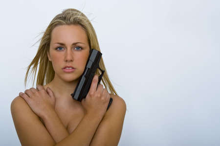 A stunningly beautiful young woman posing  with a handgun