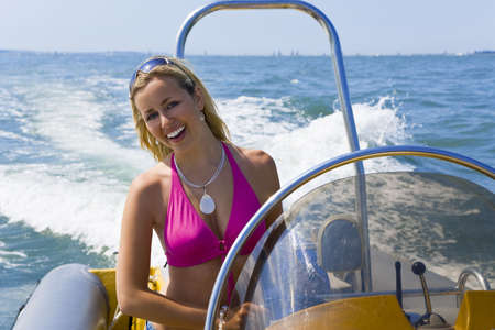 A stunningly beautiful young woman driving a powerboat and having fun. photo
