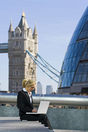 A beautiful young female executive working on her laptop in London, England, with her mobile phone beside her and Tower Bridge and Canary Wharf in the background Stock Photo - 1898402