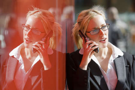 A beautiful young female executive talking on her cell phone and reflected in the red wall of a hi-tech office building photo