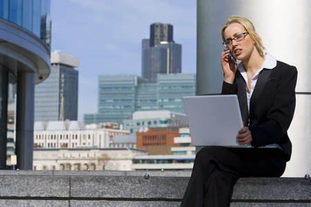 A beautiful young female executive talking on her cell phone and working on her laptop in a hi-tech urban surrounding photo