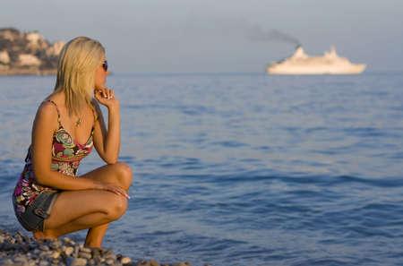 mujer mirando el horizonte: Hermosa mujer joven en una playa, mirando un crucero en el horizonte