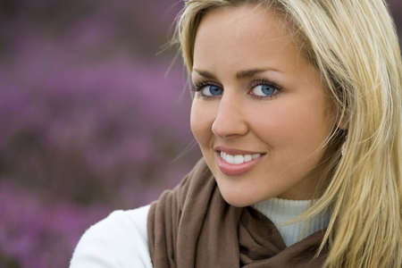 A naturally beautiful young blond woman shot in a field of out of focus heather