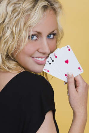 A beautiful young blond woman smiling with a hand of four aces