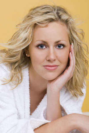 restful: Studio shot beautiful young blond woman wearing a bathrobe looking restful and relaxed